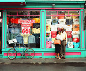 Couple posing in front of shop window — Stock Photo
