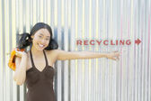 Portrait of woman pointing to recycling sign — Stock Photo