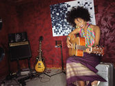 Young woman playing guitar in studio — Stock Photo