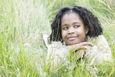Young girl lying in tall grass smirking — Stock Photo