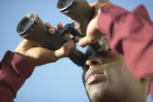 Young man looking through binoculars — Stock Photo