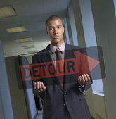 Portrait of businessman holding transparent detour sign — Stock Photo