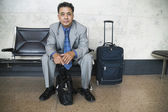 Businessman sitting in an airport with luggage — Stock Photo