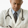 Stock Photo: Male doctor writing a prescription