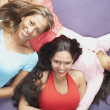 Three young women lying on couch — Stock Photo