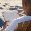 Rear view of man reading book at beach — Stock Photo
