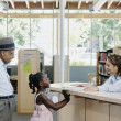 Librarian assisting girl at library — Stock Photo