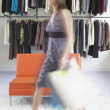 Blurred view of young woman leaving clothing store — Stock Photo
