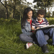Mother and son reading in meadow — Stock Photo