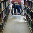 Male college student in wheelchair at library — Zdjęcie stockowe #23231612