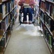 图库照片: Male college student in wheelchair at library
