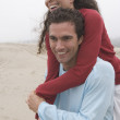 Man carrying girlfriend on his back — Stock Photo