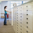 Stock Photo: Womlooking in library file drawer