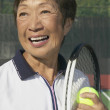 Senior Asian woman with tennis racket and ball — Zdjęcie stockowe