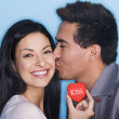 Stock Photo: Man kissing woman holding kiss cookie