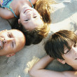 Portrait of a family lying on beach sand - Stock Photo