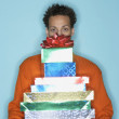 Young man behind stack of gifts - Stock Photo