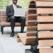 Businessman outdoors using laptop — Stock Photo