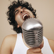 Young man singing into a microphone — Stock Photo