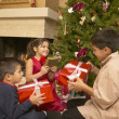 Hispanic siblings shaking Christmas gifts — 图库照片