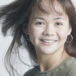 Asian woman smiling with hair blowing - Stock Photo