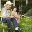 Elderly man sitting in lawn chair helping granddaughter spray water - Foto Stock