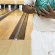 Stock Photo: Midsection of mholding bowling ball