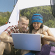 Couple with laptop in tent — Stock Photo