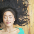 Asian woman laying on floor with hair fanned out - Stock Photo