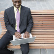 Businessman sitting outdoors using laptop — Stock Photo