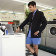 Businessman in shorts with laptop at laundromat — Stock Photo
