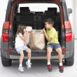 Brother and sister eating groceries in back of van - Stock Photo