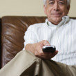 Portrait of elderly man sitting on couch with remote control in hand — Stock Photo