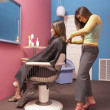 Young hairdresser cutting client's hair - Stock Photo