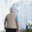 Senior man looking out window — Stock Photo