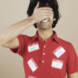 Young man covering face and wearing various name tags — Stock Photo