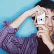 Young man taking a picture with a digital camera - Stock Photo