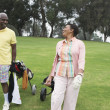 Golfing couple enjoying a laugh - Stock Photo