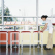Teenage girl moving stool in restaurant - Stock Photo