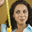 Woman looking sideways holding tape measure - Stock Photo