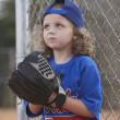 Girl with baseball mitt on sideline - Stock Photo