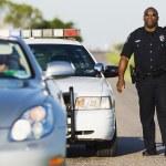 Policeman walking toward stopped convertible — Stock Photo