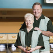 Couple with trophy at bowling alley — Stock Photo