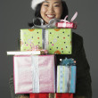 Young woman with stack of gifts - Stock Photo