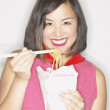 Asian woman eating Chinese takeout with chopsticks - Stock Photo