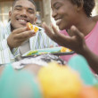 African American couple eating oranges outdoors — Stock Photo