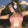 Stock Photo: Womin bikini dancing while listening to music with headphones