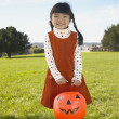 Young girl holding a pumpkin bucket — Stock Photo