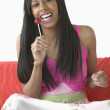 African American woman sitting on sofa with lollypop - Stock Photo