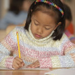 Girl writing at desk in classroom — Stock Photo